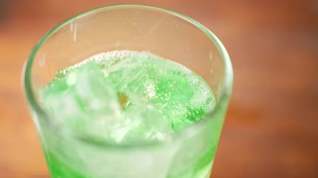 tonikum : Ice cubes falling into glass with sparkling green water. Quenching thirst and summer refreshing drink concept