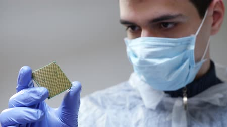 полупроводник : Engineer in a protective medical mask on the face and blue gloves holding microchip with gloves and examine it. Computer hardware, repairing, upgrade and technology concept