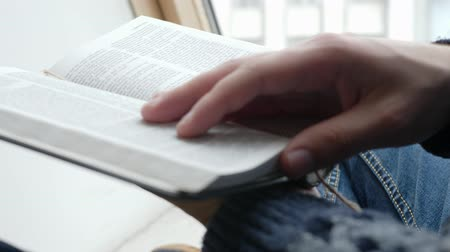 bible study : Reading and studying the Holy Bible sitting on sill
