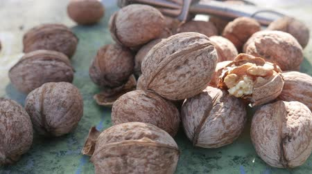 walnut shell : Kernel nut, cracked and whole walnut on old green desk in sunny day. Healthy snack food Stock Footage