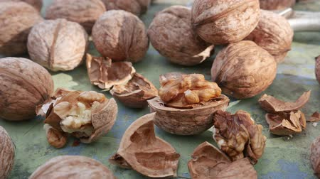 orzech : Walnut kernels and whole walnuts on rustic green old wooden table. Healthy snack food Wideo