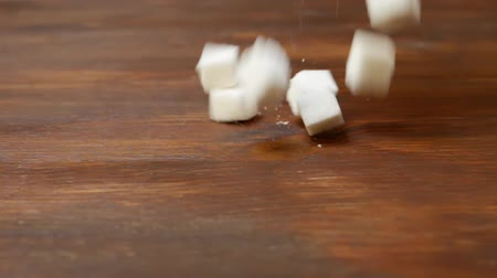 adoçante : Sugar Lumps Fall Down On Brown Wooden Table Dolly Moves Left