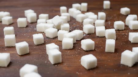 sweetener : White sugar cubes on wooden brown background