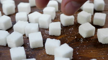 adoçante : Lumps of Sugar Taken from Wooden Table by Mans Hand