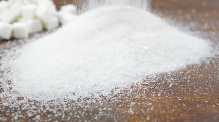 sweetener : White granulated sugar and refined sugar on brown wooden surface