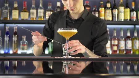 bourbon whisky : Barman making alcoholic drink into glasses on bar counter on blurred background Stock mozgókép