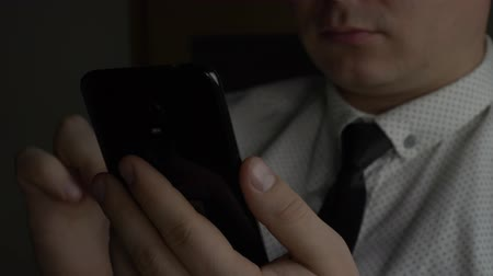 домашний интерьер : Manager or businessman in white shirt with blue tie using black smartphone at dark office at late work. Concept of young people working mobile devices
