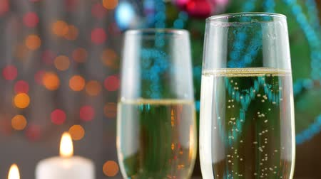 champagne flute : Champagne pouring and foaming in glasses over holiday bokeh green background. Success Christmas celebrating