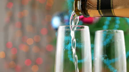 cidra : Champagne pouring and foaming in glasses from bottle with blinking lights and Christmas tree background