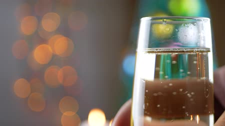 крошечный : Champagne pouring and foaming in glasses over holiday bokeh green background. Success Christmas celebrating