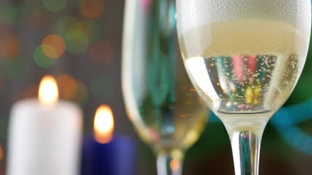champagne bottles : Champagne pouring and foaming in glasses over white and blue candles are burning, blinking and Christmas tree background. Success Christmas celebrating Stock Footage