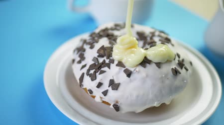 geçiştirmek : Condensed Milk Flows on Sweet Donut with Glaze on Blue Table with Cup of Coffee
