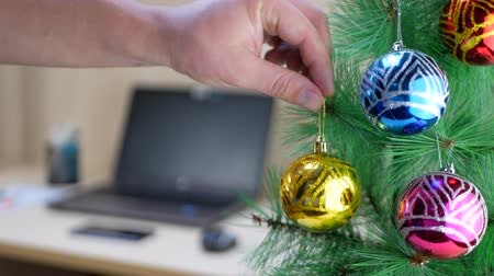pozlátko : Manager hanging gold or yellow Christmas ball on Christmas tree in office at work place background Dostupné videozáznamy