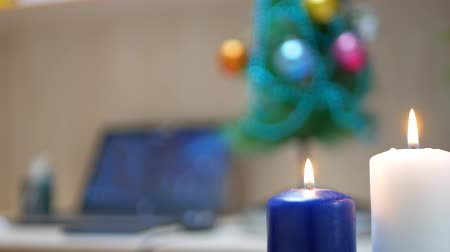 świecznik : White and blue candles are burning in office at work place with notebook and Christmas tree background