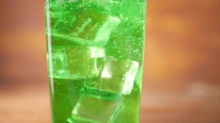 chladič : Ice cubes falling into glass with sparkling green water. Quenching thirst and summer refreshing drink concept
