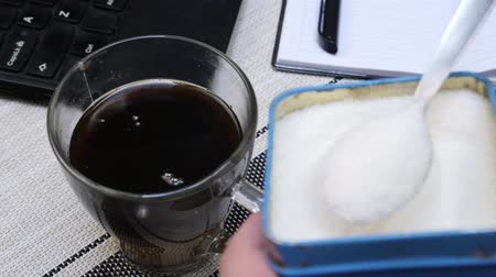 glicose : Throwing by spoon lot of sugar into cup of coffee on table with laptop and notepad in office. Concept of getting diabetes Vídeos