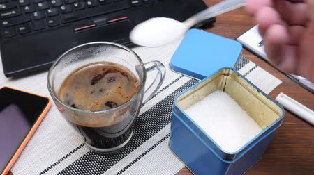 adoçante : Hand puts lot of sugar in cup of hot coffee on table with black laptop, notepad and pens in office. Concept of getting diabetes at break time Vídeos