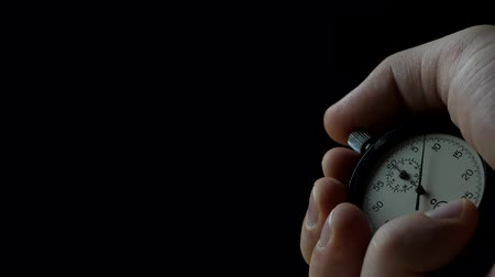 güvenilirlik : Analogue Stopwatch in Hand on the Black Background. Time Start with Old Chronometer. Man Presses Start Button in the Sport Concept Stok Video