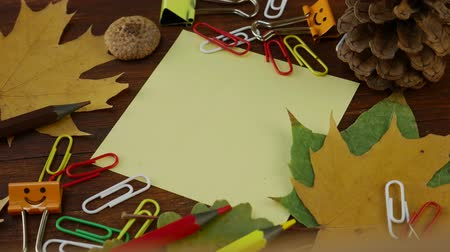 záložka : Yellow sheet of paper on brown wooden table with yellow fallen maple leaves and school stationery. Concept of back to school or education in the fall in September or October