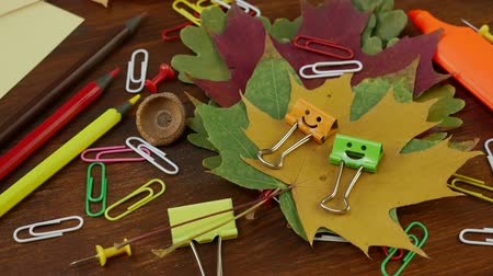 ordner : Smiles Binder Clips on Yellow Fallen Maple Leaves and School Office Supplies on brown wooden table. Concept of back to school or education in the fall in September or October