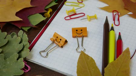 de volta : Smiles Binder Clips on Fallen Maple Leaves and School Office Supplies on brown wooden table. Red yellow and brown pencils, paper clips and notebook. Concept of back to school Vídeos