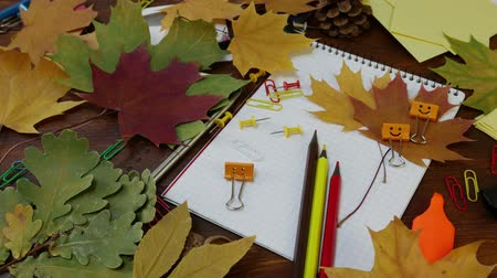 ordner : Smiles Binder Clip with Fallen Maple Leaves and School Office Supplies. Red yellow and brown pencils, paper clips and notebook on brown wooden table. Concept of back to school