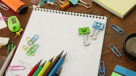 záložka : Smiles blue and green binder clips on notebook, multi-colored pencils, paper clips, pen, chips, magnifier on brown wooden table. Concept of back to school, education and school stationery
