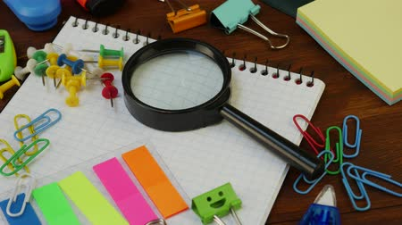 záložka : School stationery on brown wooden table: magnifying glass, multi colored pencils, paper clips and pencil sharpener, green smiles binder clips. Concept of education, back to school or knowledge