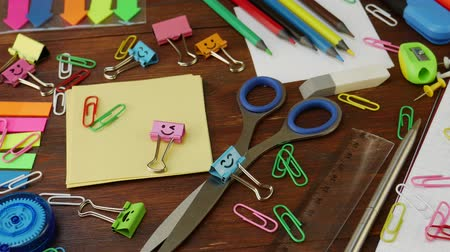 papírnictví : School stationery on brown wooden table: colored pencils, scissors and paper clips, ruler and pencil sharpener, yellow paper and smiles binder clips. Concept of education or knowledge, back to school