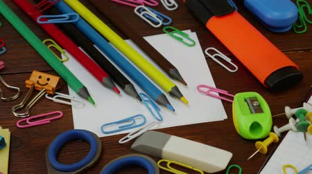 borracha : School stationery on brown wooden table: multi-colored pencils, scissors and paper clips, ruler and chips, white paper and smiles binder clips. Concept of back to school, education or knowledge