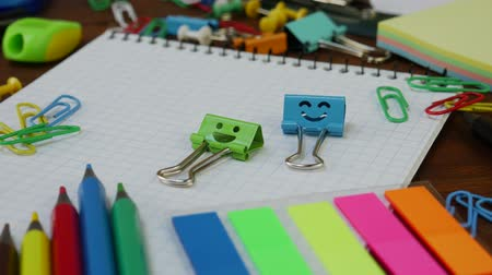papeteria : Smiles Blue and Green Binder Clips on Notebook with School Office Supplies: colored pencils and paper clips on brown wooden table. Concept of back to school and education