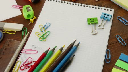 borracha : School stationery: multi-colored pencils, paper clips, ruler, pencil sharpener, magnifier, smiles blue and green binder clips on notebook. Concept of back to school and education Stock Footage