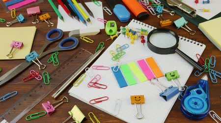 apontador : School stationery on brown wooden table and notebook: pen, scissors and paper clips, ruler and pencil sharpener, smiles binder clips. Concept of back to school, education or knowledge Stock Footage