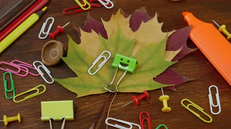 záložka : Smiles Binder Clip with Fallen Maple Leaves and School Office Supplies. Red yellow and brown pencils, paper clips and notebook on brown wooden table. Concept of back to school