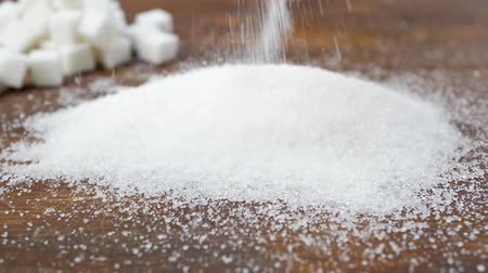 adoçante : White Sugar Falls or Pours On Brown Wooden Surface