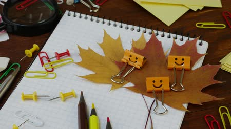 kötőanyag : Smiles Yellow Binder Clip with Fallen Maple Leaves and School Office Supplies. Red yellow and brown pencils, paper clips and notebook on brown wooden table. Concept of back to school Stock mozgókép