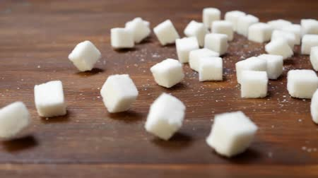 adoçante : Lump Sugar Falls Down On Brown Wooden Surface