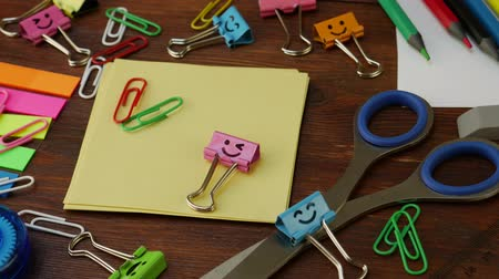 apontador : School stationery on brown wooden table: colored pencils, scissors and paper clips, ruler and pencil sharpener, yellow paper and smiles binder clips. Concept of education or knowledge, back to school