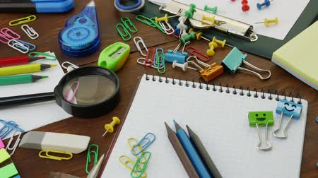 záložka : School stationery on brown wooden table: colored pencils, scissors and paper clips, ruler and pencil sharpener, yellow paper and smiles binder clips. Concept of education or knowledge, back to school
