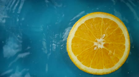 plunging : Sliced orange fruit plunging and splashes in water at green blue background. Concept of freshness juicy drink Stock Footage