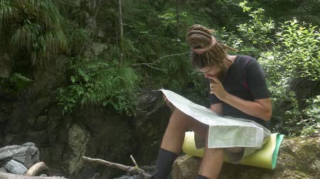hajózik : Traveler considers map in forest. Hipster male with dreadlocks examines paper map while traveling sitting on stone near mountain stream