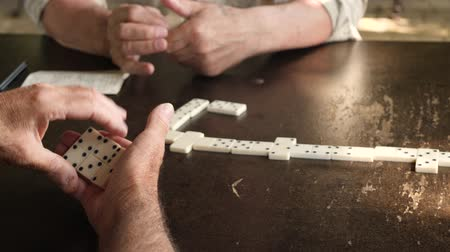 continuity : Active retired mens hands playing game of domino at table. Leisure, retirement or recreation concept