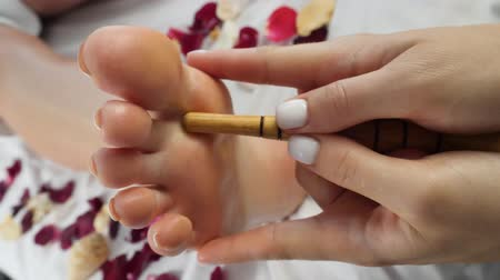 甘やかす : Female masseur hand massages the feet by wooden stick during treatment. Woman in therapy room lying on bed with rose petals. Rest in an elite beauty room. Thai massage concept
