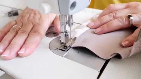embreagem : Senior female sewing cloth on machine. Work table of tailor, processing edge tulle lace curtains