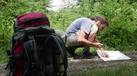 ориентация : Hipster male traveler with dreadlocks looks for paper map sitting on dirt road in forest. Hiking backpack in foreground. Trip route destination on map concept