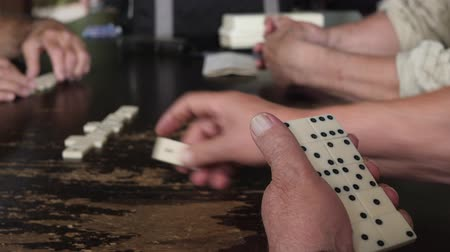 continuidad : Senior hands playing game of domino holding dominoes pieces or blocks. Leisure, retirement or recreation concept
