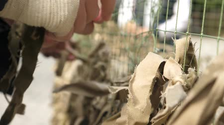 khaki : Military screening netting at army camp. Male soldier with wounded hand weaves army camouflage net