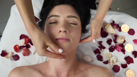 masszőr : Female masseur hand massages womanss neck, face and chin on white bed with rose petals and candle during treatment. Facial beauty treatment. Cosmetology concept. Luxury treatment at spa salon