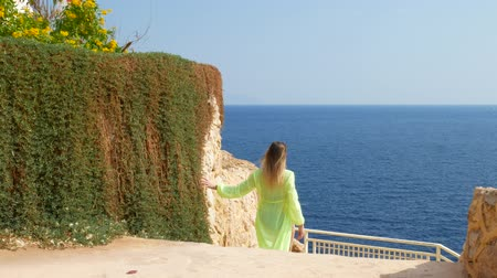 odrážející : Female in light green pareo and swimsuit walks near pattern of blue sea surface reflecting the sun. Observation deck near bay on coastline with water waves in blue sea Dostupné videozáznamy