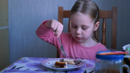 ovenschotel : Adorable Happy child girl eating cottage cheese casserole or cheesecake sitting on chair at table in home kitchen. Healthy and natural baby food Stockvideo